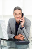 Self-assured businessman on phone at his desk — Stock Photo