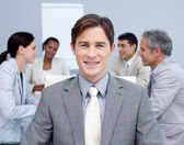 Close-up of a smiling young businessman in a meeting — Stock Photo