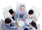 Smiling multi-ethnic business team holding a globe — Stock Photo