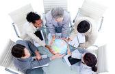 Serious international business team holding a terrestrial globe — Stock Photo