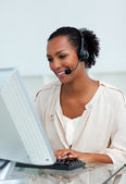 Cheerful businesswoman with headset on working at a computer — Stock Photo