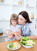 Dissatisfied little girl eating vegetables with her mother — Stock Photo
