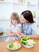 Dissatisfied blond girl eating vegetables with her mother — Stock Photo