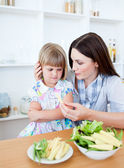 Annoyed blond girl eating vegetables with her mother — Stock Photo
