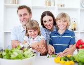 Cheerful young family cooking together — Stok fotoğraf