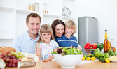 Smiling parents and their children preparing dinner together — Foto de Stock