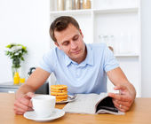 Smiling man reading a newspaper while having breakfast — Stock Photo