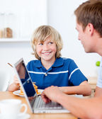 Cute boy having breakfast while his father using a laptop — Stok fotoğraf
