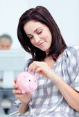 Glowing businesswoman saving money in a piggy-bank — Stock Photo