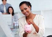 Confident businesswoman saving money in a piggy-bank — Stock Photo