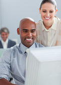 Confident businesswoman helping her colleague at a computer — Stock Photo