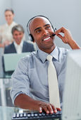 Cheerful businessman working at a computer with headset on — Stock Photo
