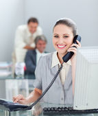 Charismatic businesswoman on phone working at a computer — Stock Photo