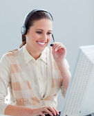 Smiling businesswoman working at a computer with headset on — Stock Photo