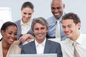 Smiling Multi-ethnic business group using a laptop — Stock Photo
