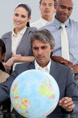 Multi-ethnic business around a terrestrial globe — Stock Photo