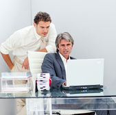 Confident manager helping his colleague work at a computer — Stock Photo