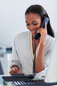Assertive ethnic businesswoman talking on a phone — Stock fotografie