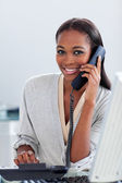 Assertive ethnic businesswoman on phone looking at the camera — Stock Photo