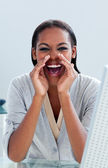 Young businesswoman yelling at her desk — Stock Photo