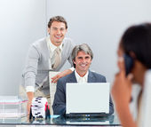 Smiling businessmen working at a computer together — Stock Photo
