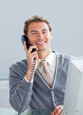 Smiling businessman on phone at his desk — Stockfoto