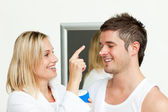 Wife putting cream on his husband's nose — Stock Photo