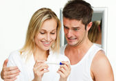 Happy woman and frightened man examining a pregnancy test — Stock Photo