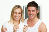 Happy couple examining a pregnancy test smiling at the camera — Stock Photo