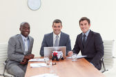 Three businessmen in a meeting smiling — Stock Photo