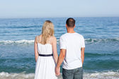 Enamored couple holding hands at the shore line — Stock Photo