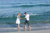 Loving couple having fun at the shore line — Stock Photo