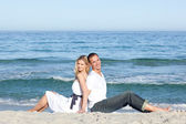 Smiling couple sitting on the sand — Stock Photo