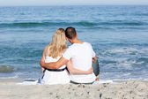 Affectionate couple sitting on the sand at the beach — Stock fotografie