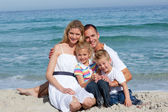 Portrait of a cheerful family sitting on the sand — Stock Photo