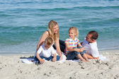 Caring parents with their children sitting on the sand — Stock Photo