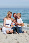 Happy children and their parents sitting on the sand — Stock Photo