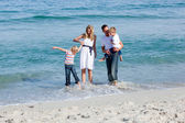 Lively family having fun at the beach — Stock Photo