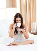 Vacker kvinna dricker kaffe sitter på sängen — Stockfoto