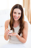Pretty woman taking a pill sitting on bed — Stock Photo