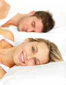 Portrait of a smiling couple sleeping on their bed — Stock Photo