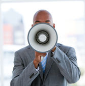 Ethnic businessman yelling through a megaphone — Stock Photo