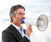 Confident businessman yelling through a megaphone — Stock Photo