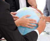 Close-up of a serious businessteam touching terrestrial globe — Zdjęcie stockowe