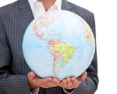 Close-up of a male executive holding a terrestrial globe — Stock Photo