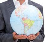 Primer plano de un ejecutivo hombre sosteniendo un globo terrestre — Foto de Stock
