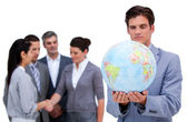 Handsome business man and his team looking at a terrestrial glob — Stock Photo