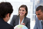Fortunate businessteam looking at a terrestrial globe — Stock Photo