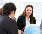 Confident businessteam looking at a terrestrial globe — Zdjęcie stockowe