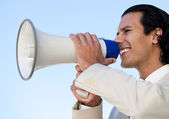 Portrait of an hispanic business man shouting through a megaphon — Stock Photo